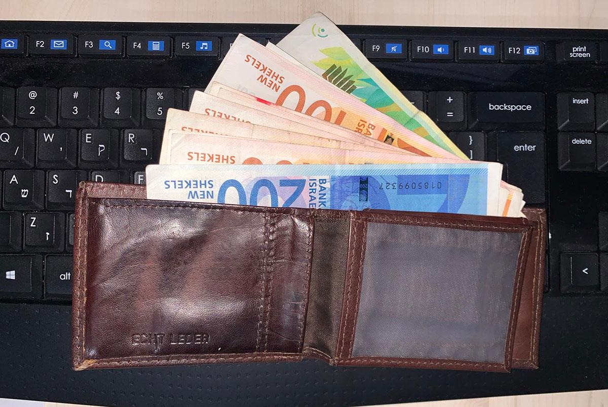 ארנק עם שטרות כסף על מקלדת